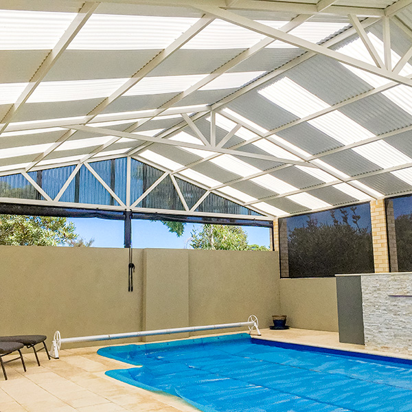 Patio with translucent polycarbonate sheets in patio roof acts as a pool enclosure.